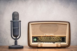 Retro broadcast table radio receiver with green eye light, studio microphone circa 1950 on wooden desk front concrete wall background. Listen music concept. Vintage instagram old style filtered photo