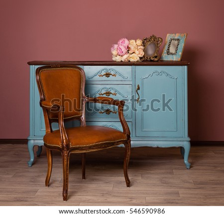 Retro brown leather armchair near blue dresser, tender bouquet and two frames. Blue and brown vintage interior. Brown room with ethnic dresser and chair. Antique cupboard. Clothes closet. Vanity Table - Shutterstock ID 546590986