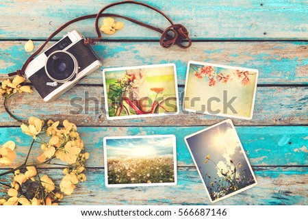 Retro camera and instant paper photo album on wood table with flowers border design - photo of remembrance and nostalgia in spring. vintage style #566687146