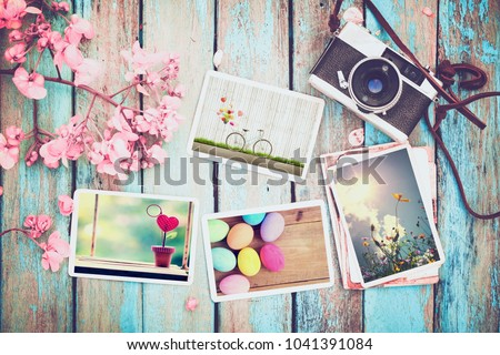Retro camera and paper photo album on wood table with flowers border design - concept of remembrance and nostalgia holiday in spring. vintage style