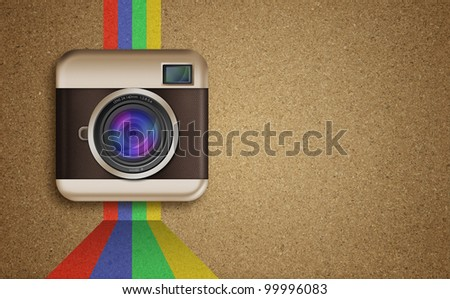 retro camera icon with rainbow colors on cork board background