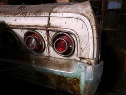 Retro car covered in debris in old barn