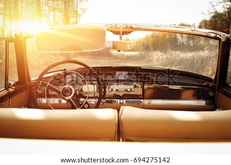 retro car in forest and golden autumn sunset time  #694275142