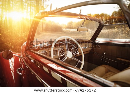 retro car in forest and golden autumn sunset time  #694275172