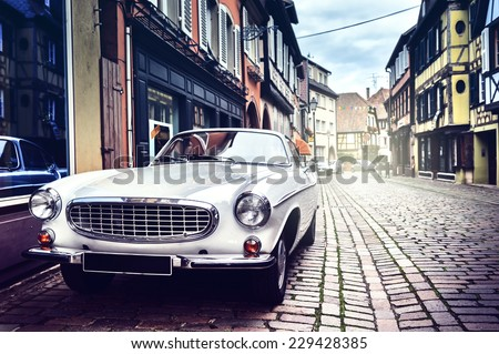 Retro car parked in old European city street #229428385