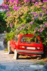 Retro car parked in street, under tree. Montenegro, Europe. Oldtimer with classical design.