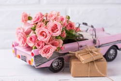 Retro car toy with pink roses and wrapped boxes with presents  flowers against  white textured  wall. Romantic background. Selective focus. Place for text.