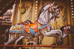 Retro carousel white / black horse. Old wooden horse carousel. Carousel! Horses on vintage, retro carnival cheerful walk. CloseUp of colorful carousel with horses. vintage photo processing