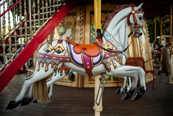 Retro carousel white / black horse. Old wooden horse carousel. Carousel! Horses on vintage, retro carnival cheerful walk. CloseUp of colorful carousel (roundabout) with horses.