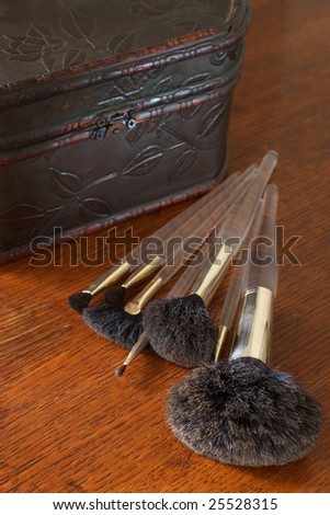 Retro casket and make-up brushes on wood dressing table. Selective focus (large brushes).
