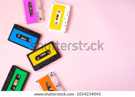 Retro cassette tape collection on pink background, top view, copy space.