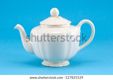 retro ceramic white teapot dish on blue background. - stock photo