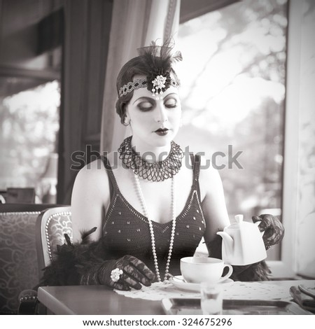 Retro Charleston Woman Sitting with in a Restaurant Holding a Cup of Tea. Black and White Portrait of The Beautiful Retro Woman Drinking Tea in Cafe in Black Lace and Accessories in Style 1920 - 1930