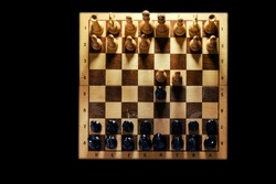 Retro chess board with figures from USSR on a black background. Chess opening Queen Gambit, top view