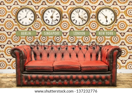 Retro chesterfield sofa with world time clocks on a wall with vintage wallpaper
