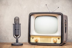 Retro classic old outdated TV receiver and aged microphone from circa 50s on wooden table front textured concrete wall background. Vintage style filtered photo