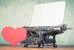 Retro classic old typewriter with paper sheet and handmade heart shape on wooden desk front textured concrete wall background. Valentines day love letter concept. Vintage style filtered photo