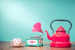 Retro classic red kettle, old fashioned gramophone radio and a cup of tea on oak wooden table in front aquamarine wall background. Old style filtered photo