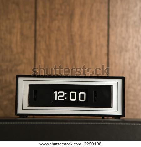 Retro clock set for 12:00 against wood paneling.