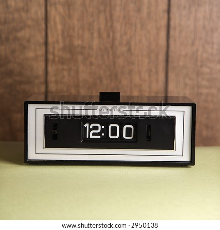 Retro clock set for 12:00 against wood paneling.