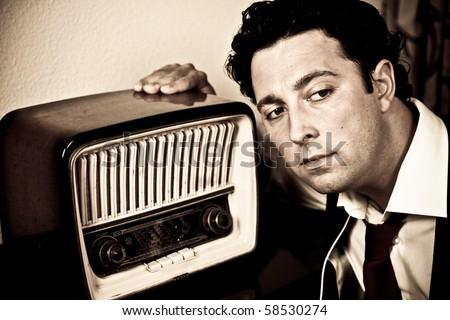 Retro - close up of dressed up man listening to old radio
