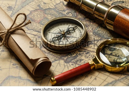 Retro compass with old map and spyglass #1085448902