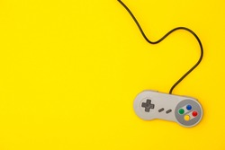 Retro computer gaming controller on a bright yellow background