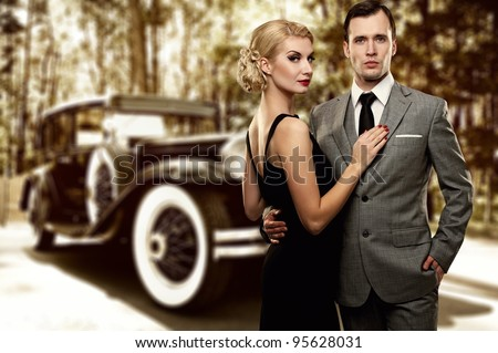 Retro couple against old car.