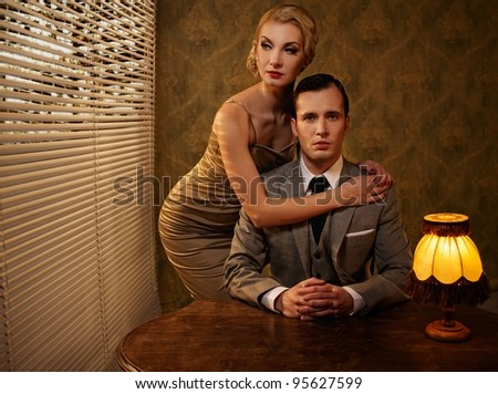Retro couple behind table.