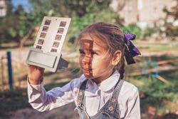 Retro device, soviet stereoscope, stereo vision. Cute girl watching 3D pictures with vintage slide viewer on the playground, past and future, happy moments and recollections
