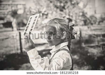 Retro device, soviet stereoscope, stereo vision. Cute girl watching 3D pictures with vintage slide viewer on the playground, past and future, happy moments and recollections ストックフォト ©