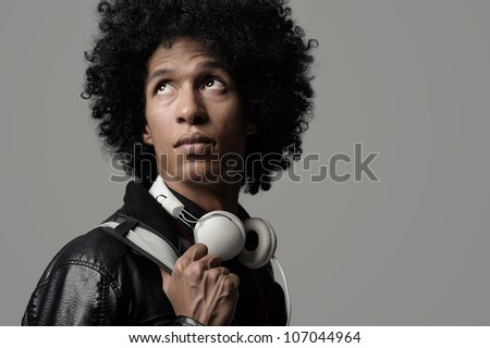 Retro dj portrait in fashion style isolated on grey background in studio. Modern music man with afro hairstyle, headphones and vinyl record.