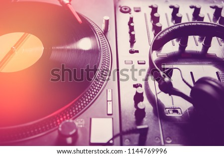 Retro dj turntable player with vinyl analog disc.Vintage record with music on turn table.Sound mixer with professional headphones for playing music on concert in night club.Techno djs equipment