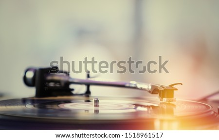 Retro dj turntable playing vinyl record with music.Vintage analog disc jockey player on concert stage.Old hi-fi audio equipment.Professional turntables on party.Film color filter & light leak effect.