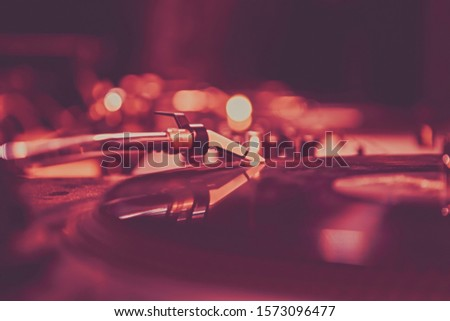 Retro dj turntable plays vinyl in red stage lights.Professional vintage disc jockey audio equipment on party.Old style analog vinyls player device on concert event in nightclub.Pro hip hop djs setup