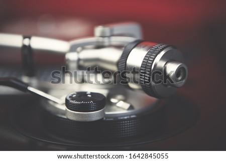 Retro dj turntables tone arm weights in close up.Professional disc jockey audio equipment in sound recording studio.
