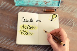 Retro effect and toned image of a woman hand writing a note with a fountain pen on a notebook. Handwritten text CREATE AN ACTION PLAN next to yellow lighting bulb as symbol for bright idea.
