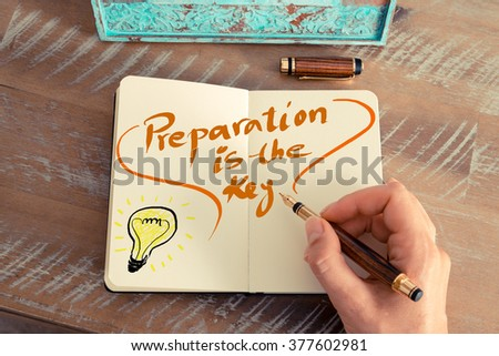 Retro effect and toned image of a woman hand writing a note with a fountain pen on a notebook. Handwritten text PREPARATION IS THE KEY next to yellow lighting bulb as symbol for bright idea. #377602981