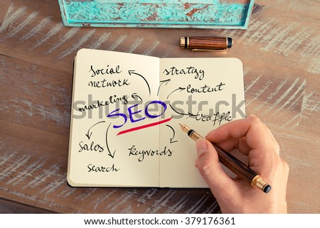 Retro effect and toned image of a woman hand writing a note with a fountain pen on a notebook. Business concept image with handwritten text SEO as SEARCH ENGINE OPTIMIZATION #379176361
