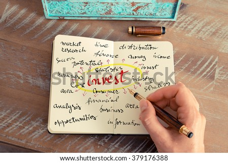 Retro effect and toned image of a woman hand writing a note with a fountain pen on a notebook. Business concept image with handwritten text INVEST #379176388