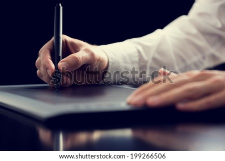 Retro effect faded and toned image of a graphic designer working with digital tablet pen, over black background.