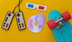 Retro entertainment, gadgets and devices. Gamepads, cruiser board, Cd's, 3D glasses on yellow background. 80s. Top view. Flat lay