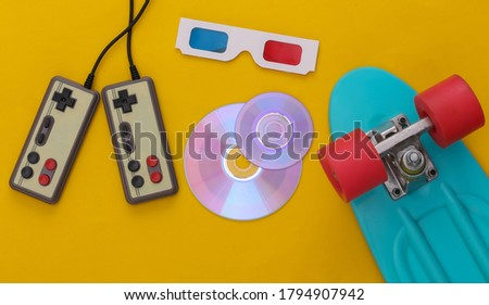 Retro entertainment, gadgets and devices. Gamepads, cruiser board, Cd's, 3D glasses on yellow background. 80s. Top view. Flat lay stock photo