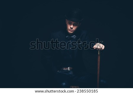 Retro fashion man with blue shirt, jacket, jeans and bow tie. Wearing black hat. Holding cane. Sitting on vintage wooden box. Studio shot against black.
