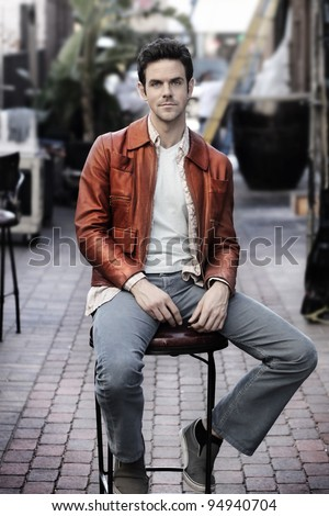 Retro feel portrait of young man outdoors in leather jacket sitting in chair