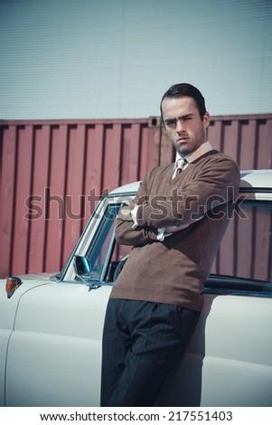 Retro fifties business fashion man leaning against vintage car.