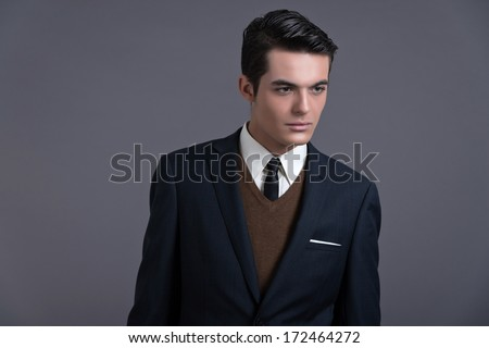 Retro fifties business fashion man with dark grease hair. Wearing dark blue suit and tie. Studio shot against grey. ストックフォト ©