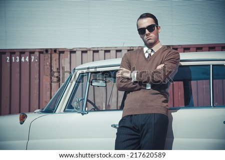Retro fifties business fashion man with sunglasses leaning against vintage car.