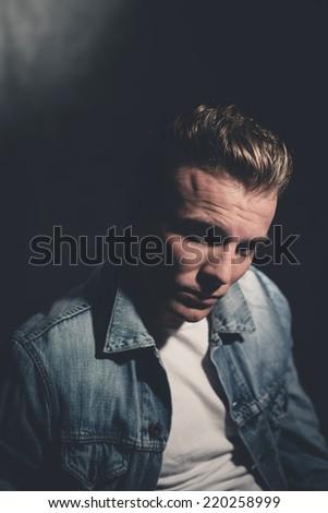 Retro fifties cool rebellion fashion man wearing white shirt and jeans jacket. Gray wall.