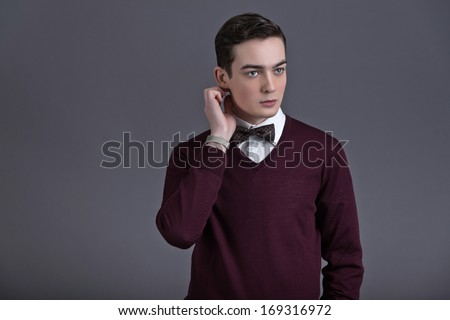 Retro fifties english style fashion young man. Wearing dark red shirt and bow tie. Studio shot against grey.